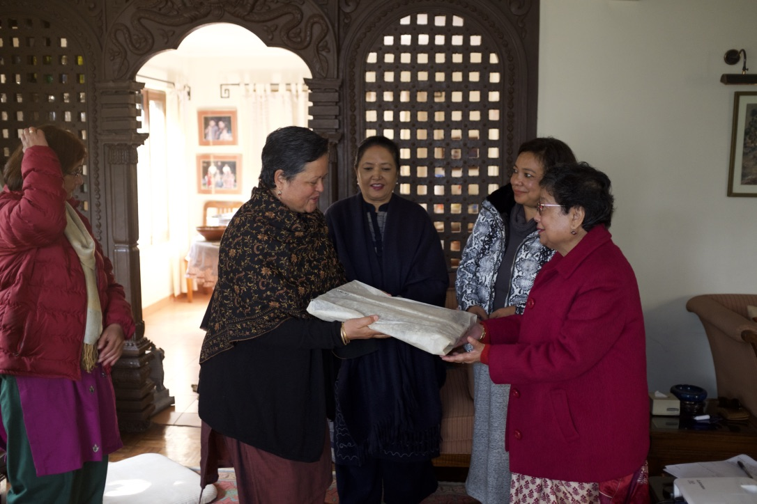 Rita Thapa presents a token of appreciation of historical gift to PBM&LC.