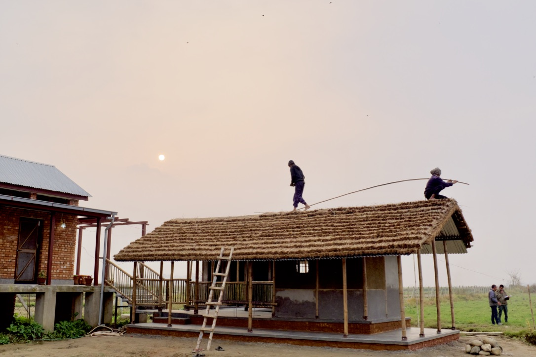 Community men work on the roofing of the outdoor kitchen.